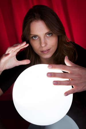 adivino: Adivino hermosa joven con sus manos alrededor de una bola brillante como lo predice el futuro y lo que tiene