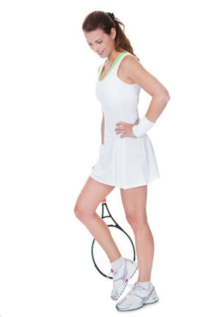 Young woman tennis player in a short white tennis dress carrying her racquet isolated on white photo