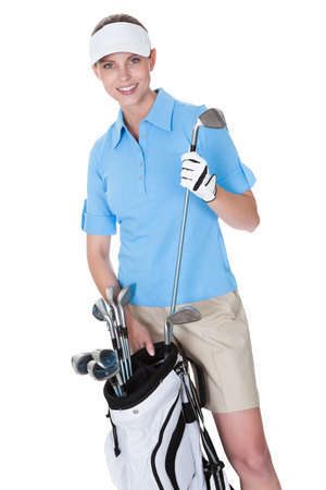 woman golf: Attractive female golfer in golf clothing with a bag of clubs selecting an iron isolated on white