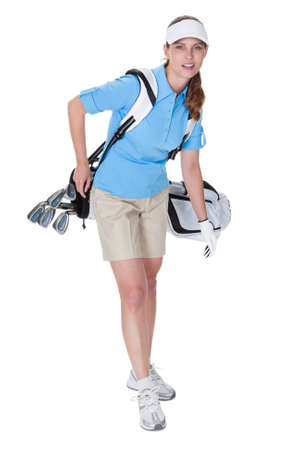Attractive female golfer in golf clothing with a bag of clubs selecting an iron isolated on white photo