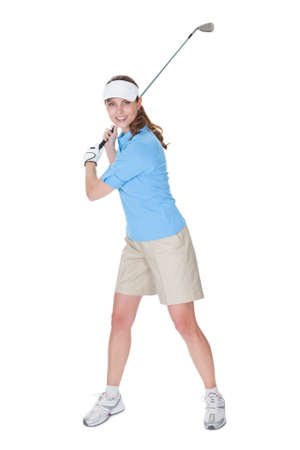 Attractive female golfer in golf clothing with a golf club isolated on white photo