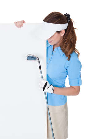 Attractive smiling female golfer holding a golfclub and a large blank board with copy-space for your advertising and marketing photo