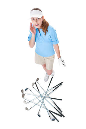 aghast: Female golfer looking aghast at a pile scattered clubs which have fallen out of her golf bag