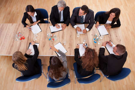 board room: Overhead view of a group of professional business people in a meeting seated around a wooden table with their notepads Stock Photo