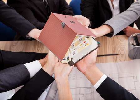 Multiple hands of diverse business people supporting a model house conceptual of partnership and teamwork Stock Photo