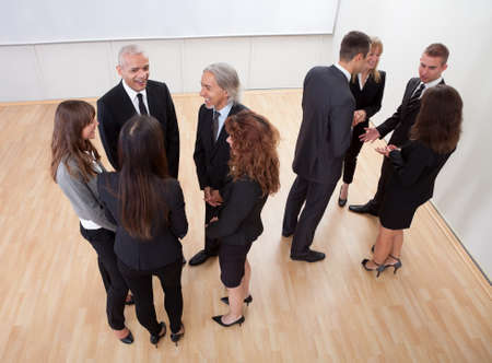 socializing: High angle view of professional business people standing around in informal groups chatting as they wait for a meeting Stock Photo