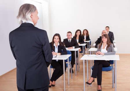 Inhouse business training in een bedrijf met een senior executive met zijn rug naar de camera geven van een presentatie Stockfoto
