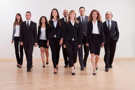 personas caminando: Gran grupo diverso de empresarios que se acercan caminando hacia la c�mara dirigido por una mujer sonriente