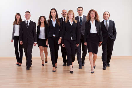 Grande gruppo eterogeneo di uomini d'affari che si avvicinano a piedi verso la telecamera guidata da una donna sorridente