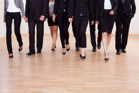 approaching: Large diverse group of business executives approaching walking towards the camera led by a smiling woman