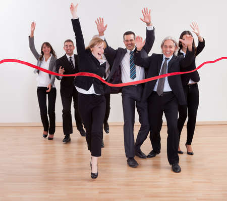 Jubilant business people celebrating raising their arms in the air and shouting as they cut the red ribbon to begin a new business venture photo