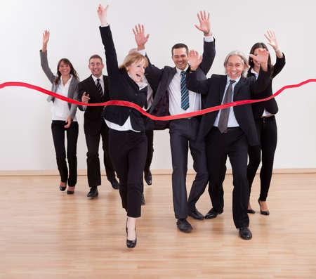 empezar: Las personas de negocios que celebran jubilosos levantar los brazos en el aire y gritando mientras cortan la cinta roja para comenzar un nuevo negocio