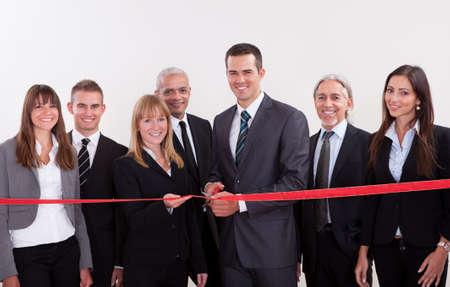 abertura: Un diverso grupo de empleados de la gerencia de negocio a nivel de punto de cortar la cinta roja y poner en marcha un nuevo negocio