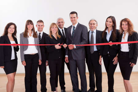 startup: A diverse group of management level business employees about to cut the red ribbon and launch a new business venture Stock Photo