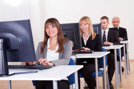 clerical: Group of diverse business people working in a support centre sitting at desks in front of computer monitors responding to email enquires