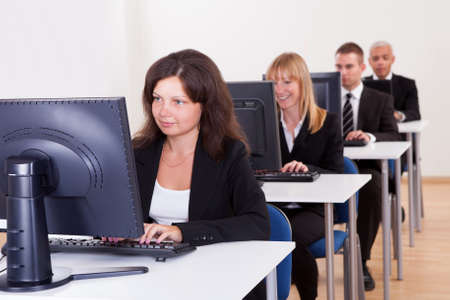 business training: Group of diverse business people working in a support centre sitting at desks in front of computer monitors responding to email enquires