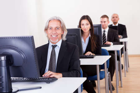 computer training: Group of diverse business people working in a support centre sitting at desks in front of computer monitors responding to email enquires