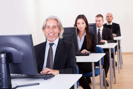servicios publicos: Grupo de gente de negocios diversos que trabajan en un centro de apoyo sentada en las mesas delante de los monitores de ordenador de responder a las inquietudes de correo electr�nico