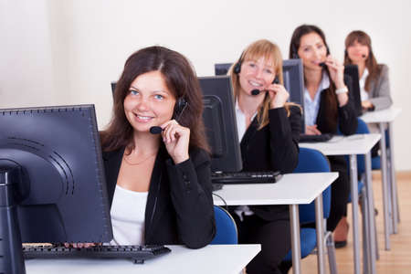 Row of attractive young telephonists seated at computers wearing headsets and microphones in a call centre or client services help desk photo