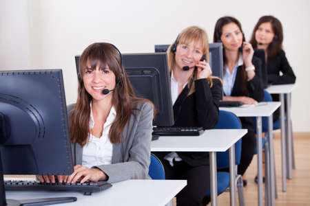 sales call: Row of attractive young telephonists seated at computers wearing headsets and microphones in a call centre or client services help desk