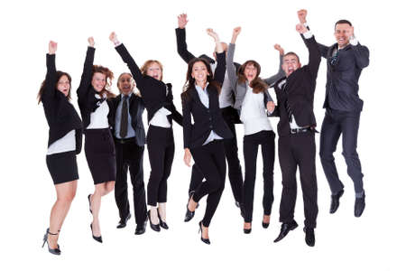 Group of jubilant business people jumping for joy and shouting in their excitement at their success isolated on white Stock Photo