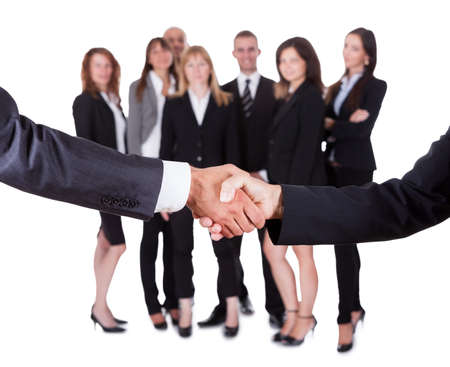 Business man and woman shaking hands watched in the background by their staff or team as they reach an agreement photo