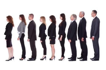 Lange lijn van diverse professionele mensen uit het bedrijfsleven staan in een wachtrij in profiel op wit wordt geïsoleerd Stockfoto