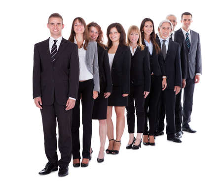 staggered: Group of confident business people in a team or partnership standing in a staggered row smiling at the camera isolated on white Stock Photo
