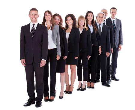 file d attente: Un groupe de gens d'affaires confiants debout dans une �quipe ou d'une soci�t� dans une rang�e d�cal�e souriant � la cam�ra isol�e sur fond blanc