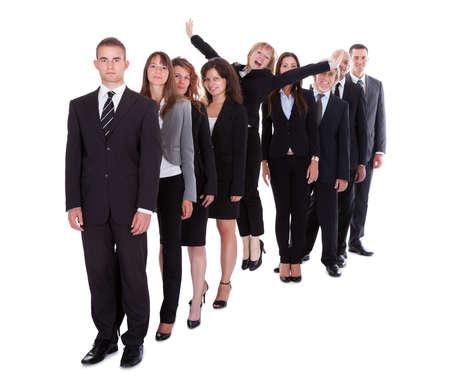 Empresaria de pie entre la multitud de sus colegas que muestra la individualidad aislada en blanco