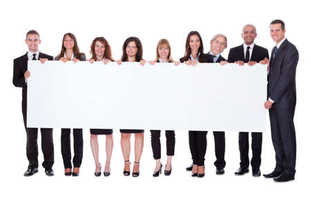 Groep van stijlvolle professionele mensen uit het bedrijfsleven staan in een lijn houdt een lange lege banner voor uw reclame of tekst