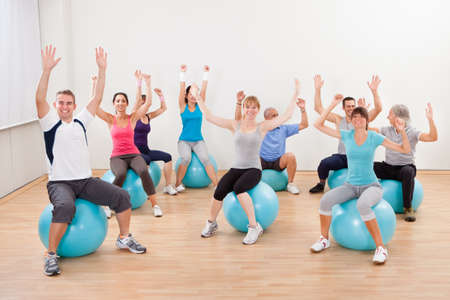 training group: Large group of people doing pilates in a gym sitting on their balls with their arms raised practicing balance Stock Photo