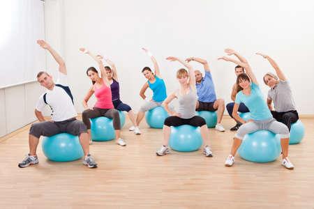 nucleo: Gran grupo de personas diversas en una clase de pilates ejercita en un gimnasio practicando equilibrio y control