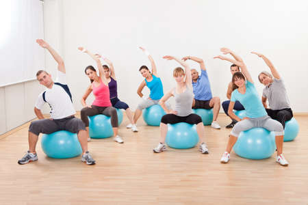 core: Large group of diverse people in a pilates class exercising in a gym practicing balance and control