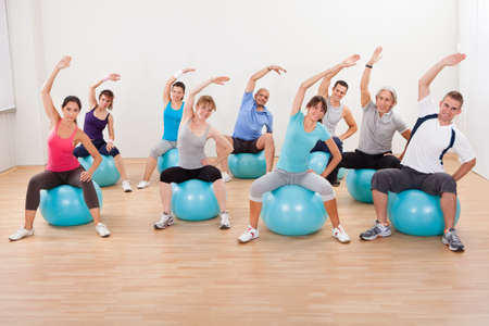 balance ball: Large group of diverse people in a pilates class exercising in a gym practicing balance and control