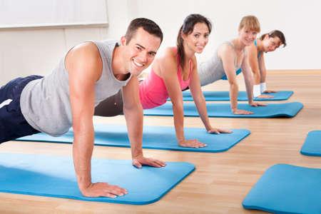 Groep van diverse gezonde mensen in een sportschool klasse doet pers ups tijdens het sporten op twee rijen van blauwe matten op een houten vloer