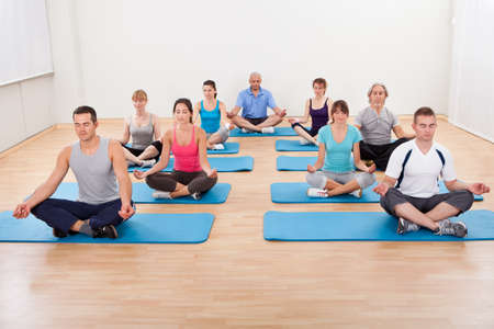 Diverse group of people practicing yoga in a gym sitting cross-legged on their mats meditating