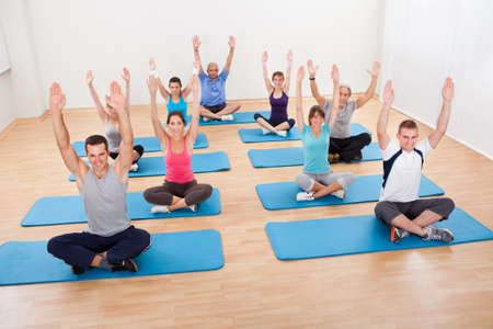 Diverse group of people practicing yoga in a gym sitting cross-legged on their mats meditating photo