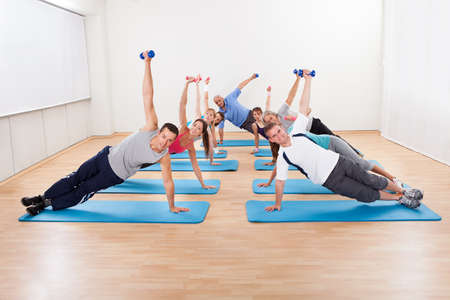 Large group of people working out in a gym balanced on one hand on their mats while raising their other arm with a dumbbell photo