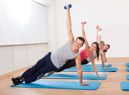working class: Large group of people working out in a gym balanced on one hand on their mats while raising their other arm with a dumbbell Stock Photo