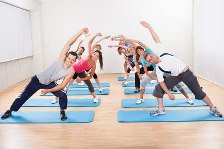 activity: Large group of diverse people doing aerobics exercises in a gym standing on blue mats