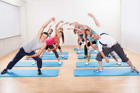 actividad fisica: Un grupo grande de gente diversa que hace ejercicios aer�bicos en un gimnasio de pie sobre alfombras azules
