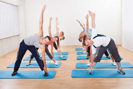 протяжение: Большая группа различных людей в классе пилатес упражнения в тренажерном ядро растяжения