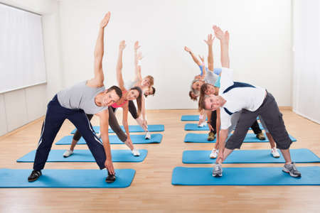 yoga class: Large group of diverse people in a pilates class exercising in a gym doing core stretching Stock Photo
