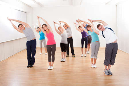 aerobics: Large group of diverse people in a pilates class exercising in a gym doing core stretching Stock Photo