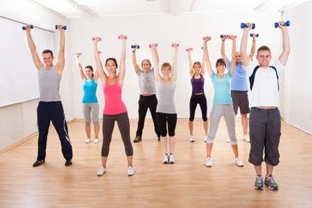 Aerobics klasse van diverse mannen en vrouwen van verschillende leeftijden uit te werken in een sportschool met halters buigen hun armspieren