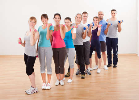 gym class: Aerobics class of diverse men and women of different ages working out in a gym with dumbbells flexing their arm muscles Stock Photo