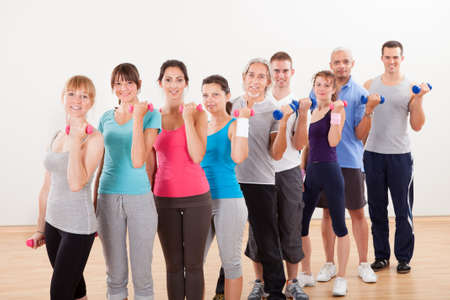 actividad fisica: Clase de aeróbicos de los hombres y mujeres de diversas edades diferentes de hacer ejercicio en un gimnasio con pesas flexionando sus músculos del brazo Foto de archivo