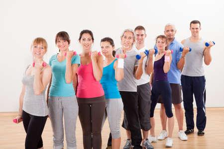 aktywność fizyczna: Class Aerobik różnorodnych mężczyzn i kobiet w różnym wieku pracuje w siłowni z hantlami zginając mięśnie ramion