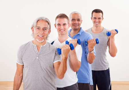 staggered: Staggered row of four men of differing ages facing the camera working out with dumbbells at a gym